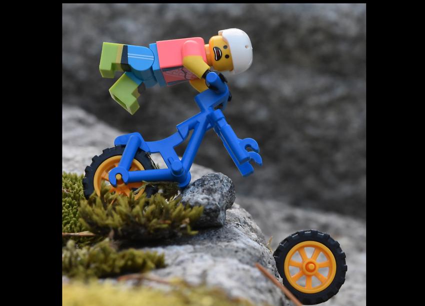 Legogubbe som cyklar i berg och tappar hjul
